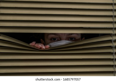 Young woman in medical mask looks out the window through the blinds