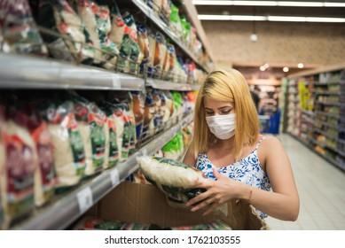 Junge Frau mit medizinischer Maske sammelt Reispackung im Supermarkt und lagert sich während einer pandemischen Korona, covid19.
