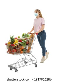 Young woman in medical mask with shopping cart full of groceries on white background