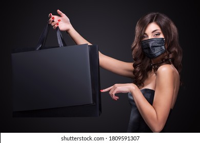 Young woman in a medical mask showing on bag in black Friday holiday. Sale and shopping concept in 2020 - time of coronavirus pandemic.