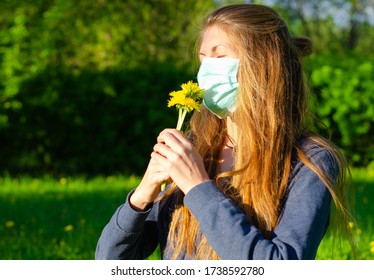 A young woman in a medical mask sniffs flowers in a Park. Spring, Allergy concept, mask mode, stop coronavirus.