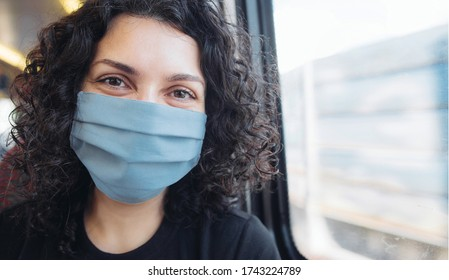 Young woman in medical mask travelling in a train, sitting next to a window. Woman smiling in a surgical mask smiling
