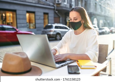 A young woman in a medical mask using laptop for work outdoors. She sits on the summer terrace at the table and talking on the phone. Quarantine coronavirus, pandemic covid