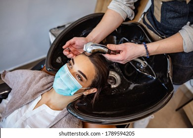 A young woman in a medical mask washes her hair in a barbershop during the covid-19 coronavirus pandemic. Reopening with security measures of Hairdressers in the Covid-19 pandemic