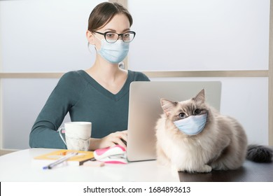 A young woman in a medical mask works on a laptop at home office and her cat in a medical mask sitting next to a laptop
