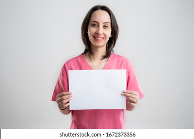 Young woman medical professional nurse or doctor dressed with pink hospital clothes, with brown hair, holding a white paper and smileing posing on a white isolated backround.