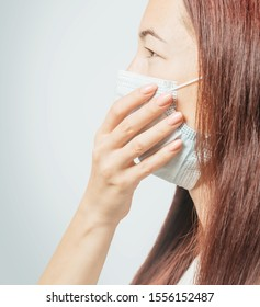 Young woman in medical protective mask against air virus, side view.