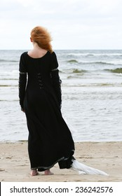 Young woman in medieval dress standing on the beach