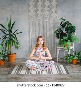 Young woman meditates in easy pose in boho interrior. Yoga at home concept