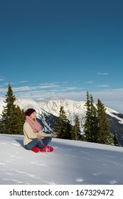 A young woman meditates in the lotus position on the snow