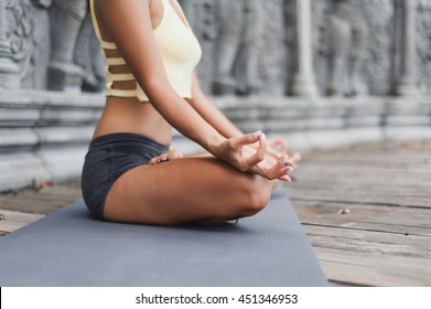 Young woman meditating in abandoned temple. Selective focus. Blurred background