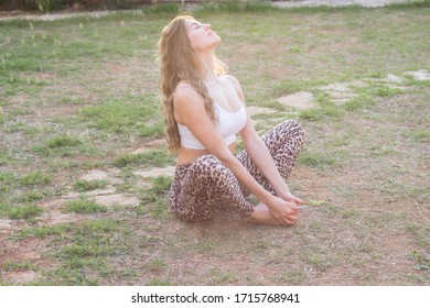 Young woman meditating in back yard on summer day