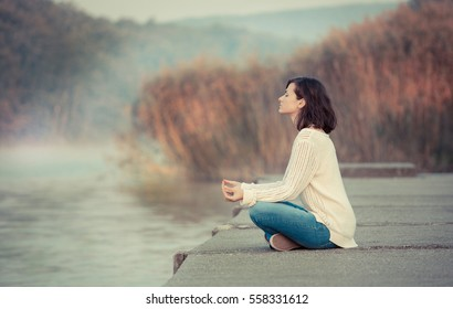 Young woman meditating by lake. Early, chilly morning.