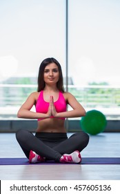 Young woman meditating in gym health concept