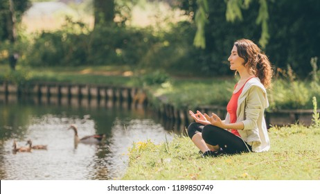 Young woman meditating in lotus or easy pose (padmasana or sukhasana) on the lawn in dutch park in Saint-Oedenrode town - work-life balance and peace of mind concept - image with copy space