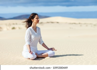 Young woman meditating in Lotus Pose in desert on Canary Islands, Spain. Padmasana. Relax concept