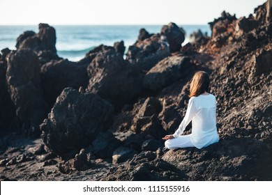 Young woman meditating in Lotus Pose in ocean beach, Canary Islands, Spain. Padmasana. Relax concept