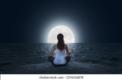 Young woman meditating in Lotus pose on the sea beach at full moon night