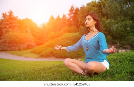 Young woman meditating in the lotus pose in the park outdoors.
