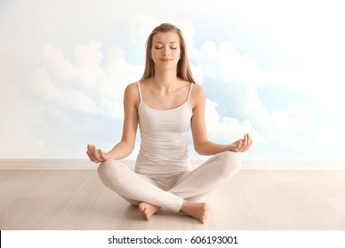 Young woman meditating in lotus pose on sky background. Concept of meditation for sleep