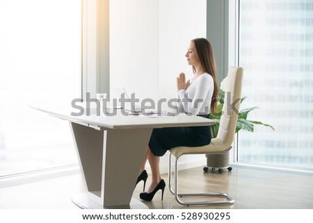 young woman meditating modern office desk の写真素材 今すぐ編集