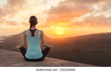 Young woman meditating from a mountain top facing beautiful sunset. Healthy mind and body.