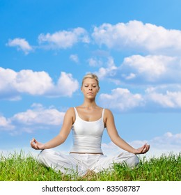 Young woman meditating on green grass with copyspace.