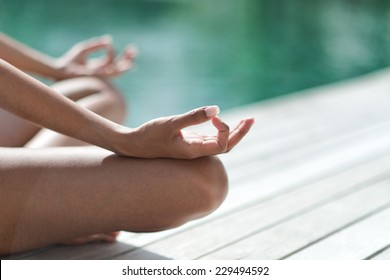 Young woman meditating on a wooden jetty or deck overlooking tranquil green-blue water, close up view of her hands and crossed legs in the lotus position