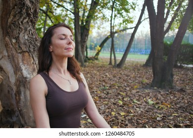 young woman meditating outdoors next to the tree