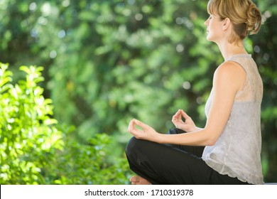 A young woman meditating outside