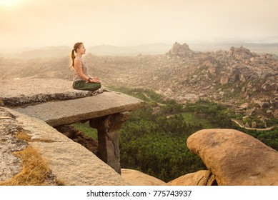 Young woman meditating over ancient city landscape on sunrise in Hampi, India. Copy space
