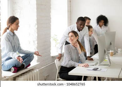 Young woman meditating practicing yoga sitting at office sill avoiding colleagues looking at girl with ironical smile, mocking and making fun of weird coworker, jeering or bullying at work concept