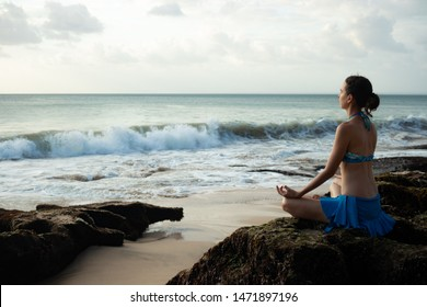 Young woman meditating, practicing yoga and pranayama with gyan mudra at the beach. Lotus yoga pose with gyan mudra. Sunset time. Caucasian woman seating on the rock. Yoga retreat in Bali, Indonesia