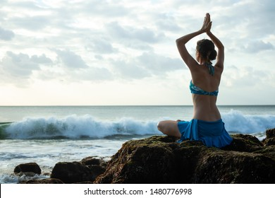 Young woman meditating, practicing yoga and pranayama with namaste mudra at the beach. Lotus yoga pose with namaste mudra. Caucasian woman sitting on the rock. Sunset time. Seascape. Yoga retreat Bali