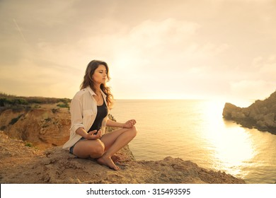 Young woman meditating at the sea