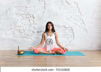 Young woman meditating in a yoga on white background, girl sits in a lotus pose on a wooden floor. Yoga and healthy lifestyle concept