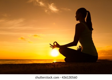 Young woman in a meditating yoga pose overlooking the beautiful sunset. Mind body spirit concept.