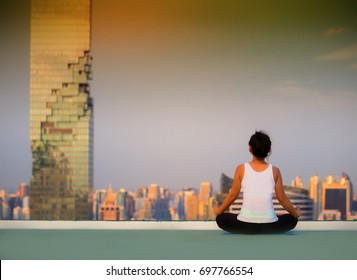 young woman meditation on the rooftop in the evening sky scene with city background