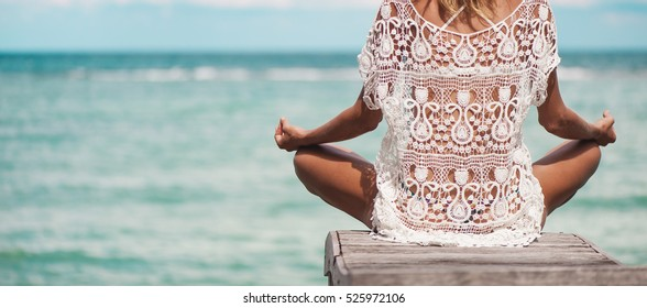 young woman meditation in a yoga pose at the beach