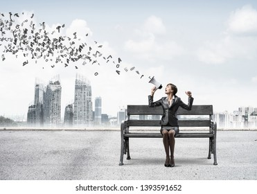 Young woman with megaphone sitting on wooden bench. Female speaker advertising new service or product on city panorama. Various letters flying out from loudspeaker. Business marketing and announcement