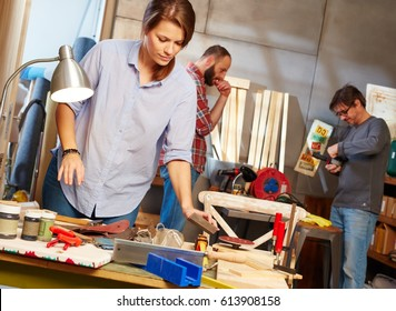 Young woman and men tinkering in workshop.