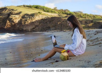 A young woman in men's white shirt working on her laptop on the Caribbean dream beach as a symbol of freedom to work whenever you want