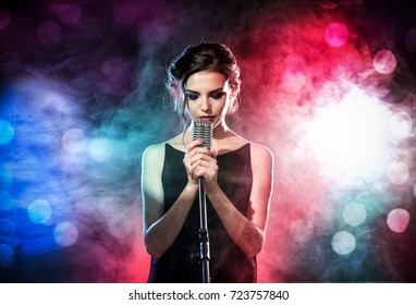 Young woman with microphone and colorful lights on concert