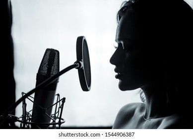 Young woman with the microphone in the recording studio. Professional vocal recording. Black and white photosession. Beautiful girl singer. Portrait. Closeup.