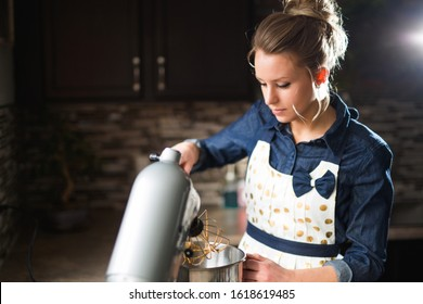 A young woman mixing ingredients in her mixer