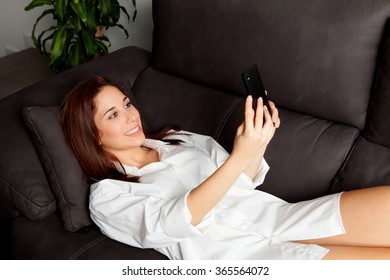 Young woman with the mobile on the sofa at home