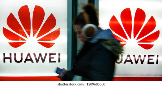 an young woman with mobile phone and headphones walks past to advertisement light boxes with Huawei logo in Kiev, Ukraine, 18 January 2019.