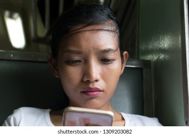 A young woman with mobile phone rides in old train. Asian girl with smartphone sits at retro wagon, Thailand.