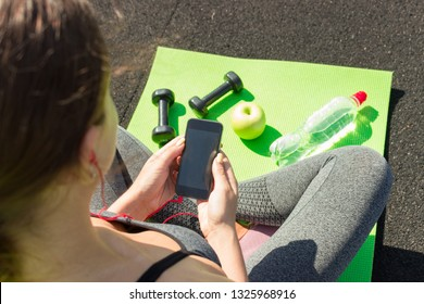 Young woman with mobile phone sitting on mat near dumbbells, apple and bottle of water on floor. Ready for workout on sity stadium. Sports and healthy concept.