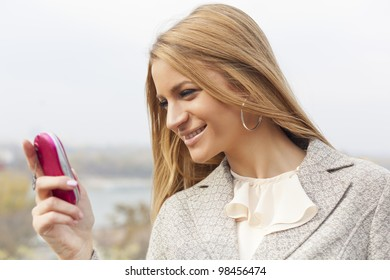Young Woman with mobile phone walking background is blurred city